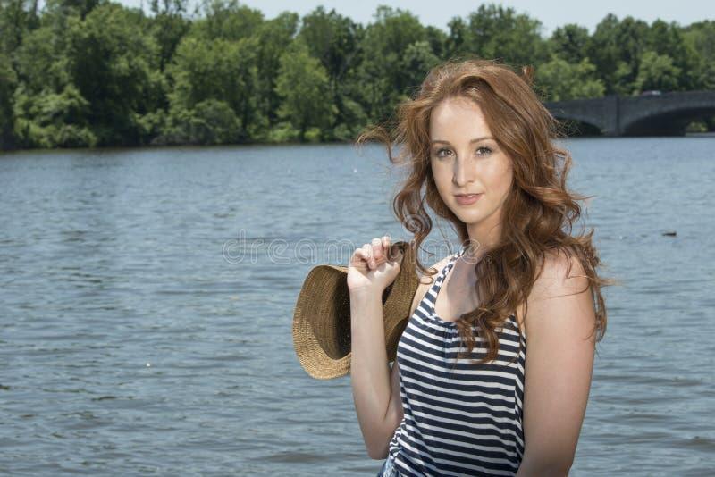 Η όμορφη redhead γυναίκα θέτει κοντά στο νερό στοκ εικόνα με δικαίωμα ελεύθερης χρήσης