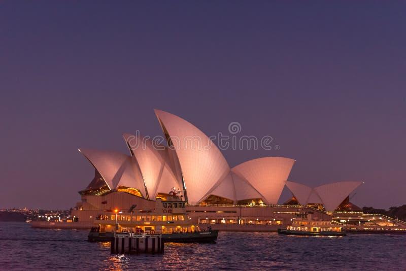 Η Όπερα του Σίδνεϊ άναψε επάνω ενάντια σε έναν σκούρο μπλε και πορφυρό ουρανό στοκ εικόνες με δικαίωμα ελεύθερης χρήσης