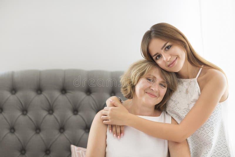 Η ώριμη γυναίκα αγκαλιάζει με το νέο κορίτσι εφήβων στοκ εικόνες