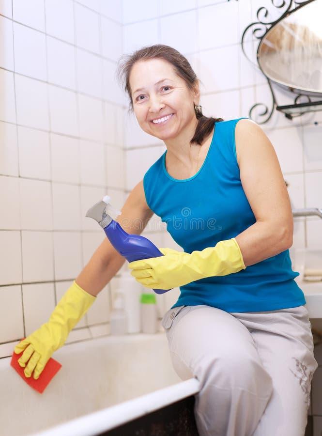 Η ώριμη γυναίκα καθαρίζει την μπανιέρα στοκ φωτογραφία με δικαίωμα ελεύθερης χρήσης