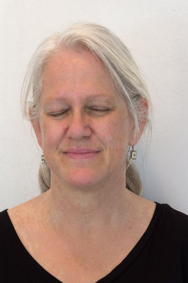 Η ώριμη γυναίκα, φυσική κανένα makeup, μάτια έκλεισε την αναμονή μιας έκπληξης, ουδέτερο υπόβαθρο στοκ φωτογραφία