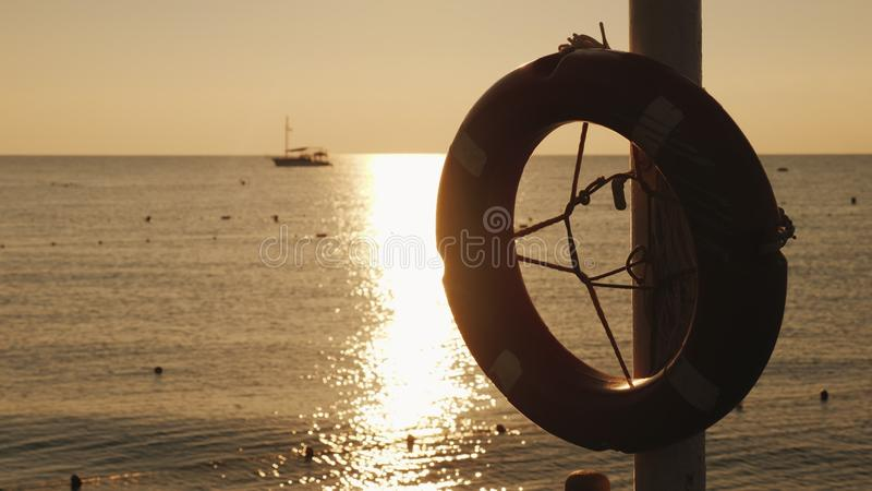 Η Dawn στη θάλασσα, στο πρώτο πλάνο κρεμά ένα δαχτυλίδι ζωής, στην απόσταση το σκάφος είναι ορατό Φυσικό τοπίο νωρίς στοκ φωτογραφίες με δικαίωμα ελεύθερης χρήσης