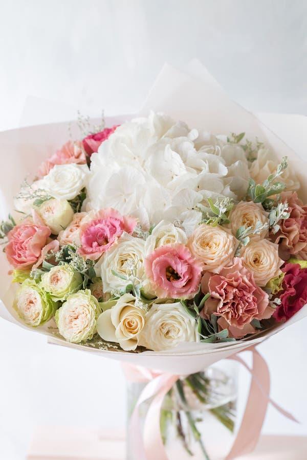 Η Floral σύνθεση με τα τριαντάφυλλα και το μίγμα ανθίζει στο βάζο γυαλιού σε ένα γκρίζο υπόβαθρο στοκ εικόνα με δικαίωμα ελεύθερης χρήσης