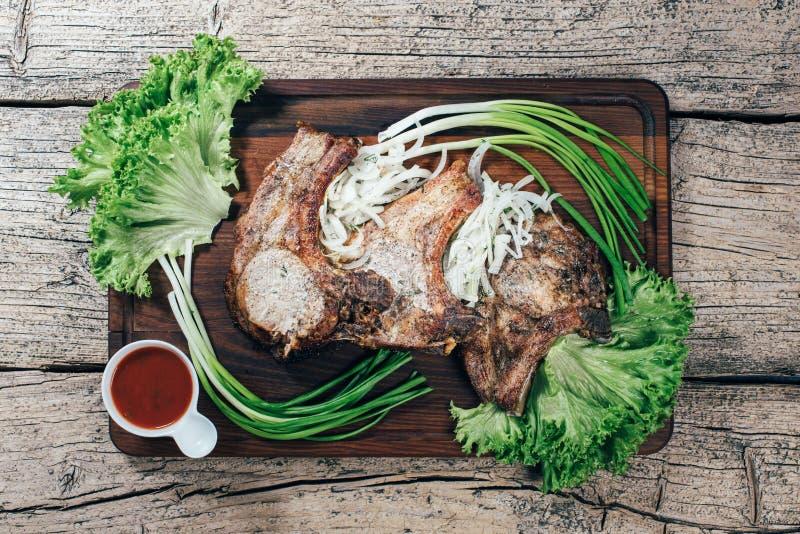 Η Juicy, ορεκτική μπριζόλα χοιρινού κρέατος παρουσιάζεται σε έναν ξύλινο πίνακα με τα πράσινα κρεμμύδια και τα φύλλα μαρουλιού στοκ εικόνες