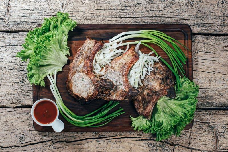 Η Juicy, ορεκτική μπριζόλα χοιρινού κρέατος παρουσιάζεται σε έναν ξύλινο πίνακα με τα πράσινα κρεμμύδια και τα φύλλα μαρουλιού στοκ φωτογραφία με δικαίωμα ελεύθερης χρήσης