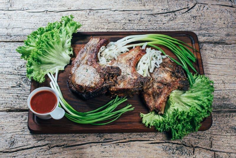 Η Juicy, ορεκτική μπριζόλα χοιρινού κρέατος παρουσιάζεται σε έναν ξύλινο πίνακα με τα πράσινα κρεμμύδια και τα φύλλα μαρουλιού στοκ φωτογραφίες