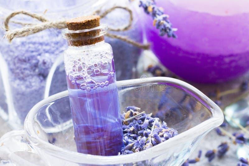 Η SPA και το wellness που θέτουν με lavender ανθίζουν, άλας θάλασσας, πετρέλαιο σε ένα μπουκάλι, κερί αρώματος στο ξύλινο άσπρο υ στοκ εικόνες