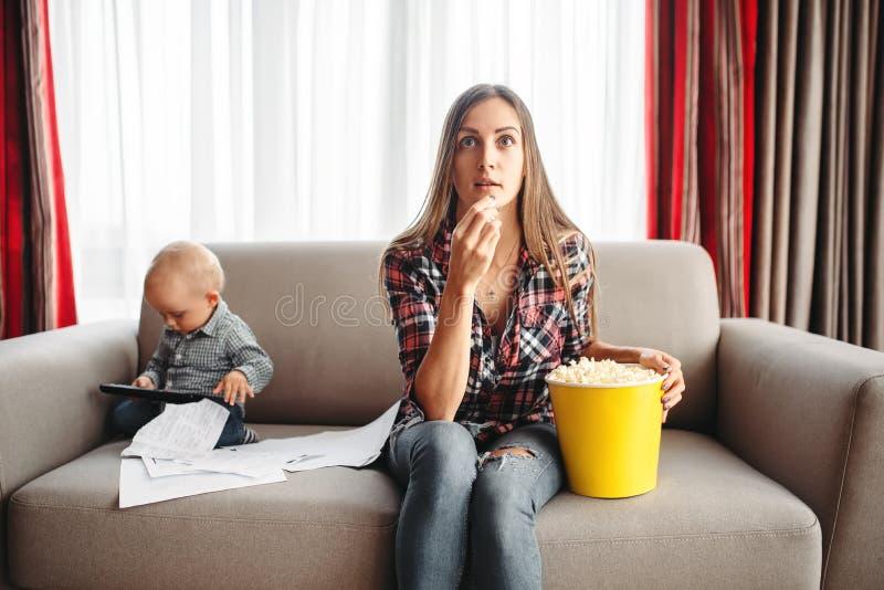 Η TV ρολογιών μητέρων και τρώει popcorn, παιδάκι πλησίον στοκ φωτογραφίες με δικαίωμα ελεύθερης χρήσης