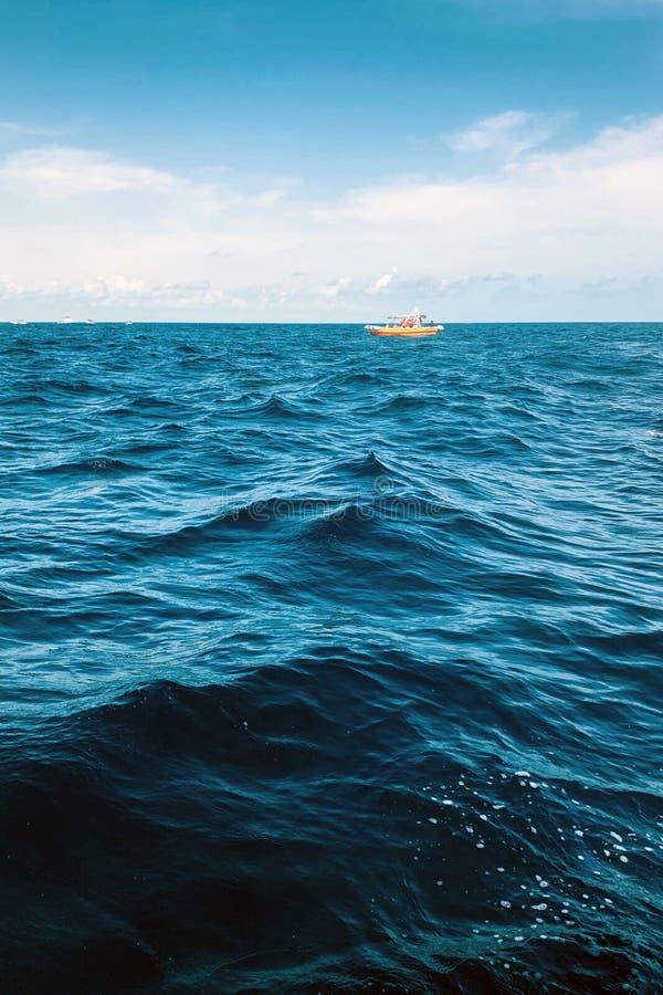 Θάλασσα και μπλε ουρανός με τα σύννεφα με τη μικρή βάρκα στοκ εικόνες με δικαίωμα ελεύθερης χρήσης