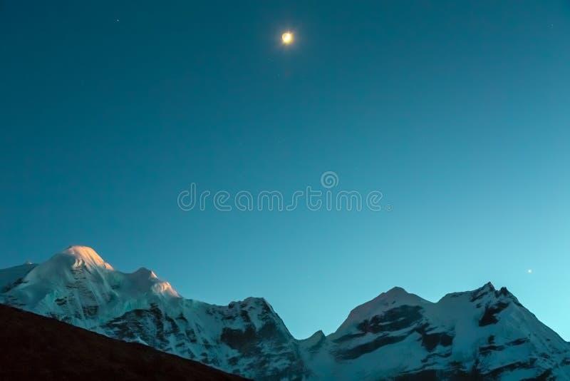 Θέα βουνού βραδιού με το ηλιοβασίλεμα και την ανατολή του φεγγαριού στοκ φωτογραφία