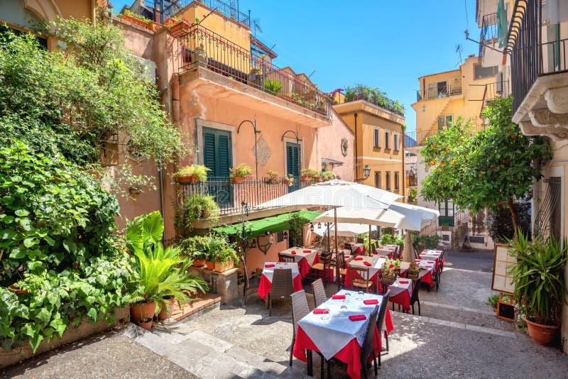 Θέα στο δρόμο με καφέ στην παλιά πόλη Ταορμίνα Σικελία, Ιταλία στοκ φωτογραφίες