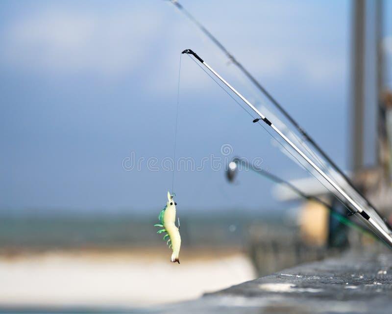 Θέλγητρο αλιείας στην αποβάθρα με την παραλία στο υπόβαθρο στοκ φωτογραφία
