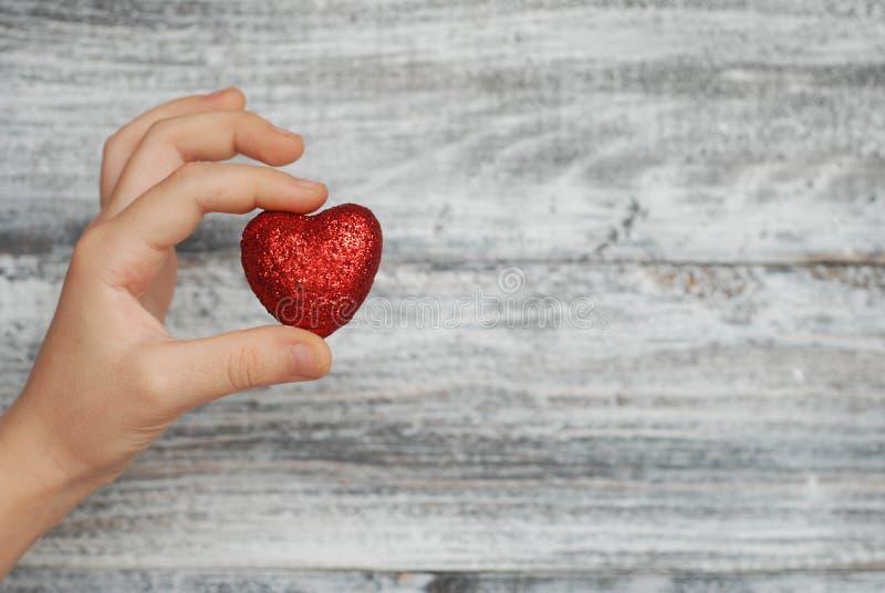 Θέμα αγάπης και καρτών χαιρετισμών: χέρι λίγο του κοριτσιού που κρατά μια κόκκινη καρδιά σε ένα ξύλινο υπόβαθρο στοκ εικόνες