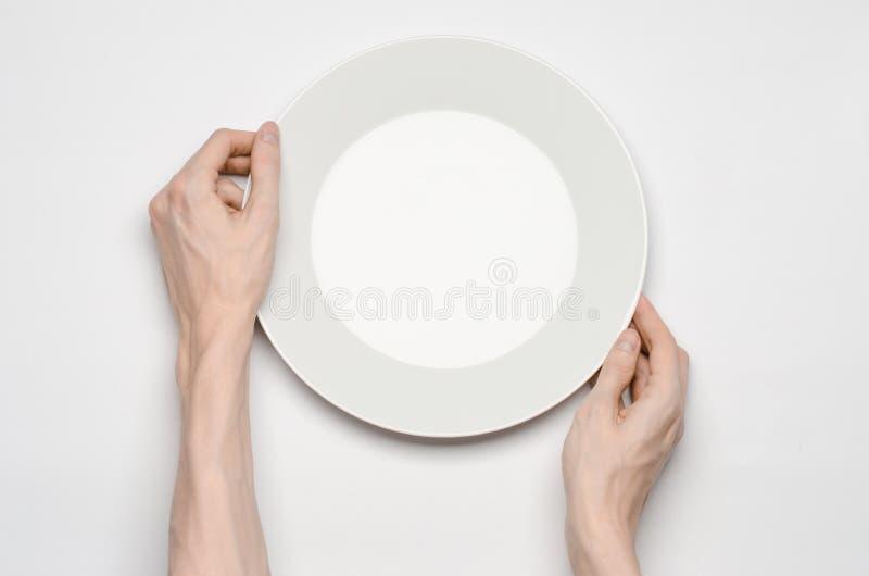 Θέμα εστιατορίων και τροφίμων: το ανθρώπινο χέρι παρουσιάζει χειρονομία σε ένα κενό άσπρο πιάτο σε ένα άσπρο υπόβαθρο απομονωμένη στοκ φωτογραφίες