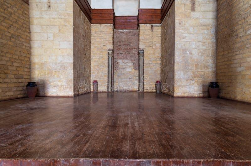Θέση δύο μαρμάρινες στήλες που περιβάλλονται με από τον τοποθετημένο τοίχο τούβλων πετρών πλαισίων και το ξύλινο πάτωμα στοκ φωτογραφίες