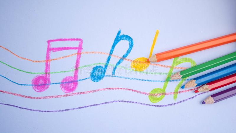 Θέση μολυβιών χρώματος στο υπόβαθρο της Λευκής Βίβλου με το σχέδιο σημειώσεων μουσικής η εκπαίδευση έννοιας βιβλίων απομόνωσε παλ στοκ εικόνες με δικαίωμα ελεύθερης χρήσης