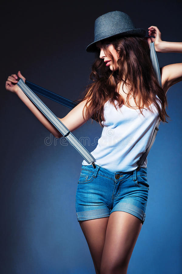 Θέτοντας προκλητική γυναίκα στο καπέλο και σορτς με suspenders στοκ εικόνες