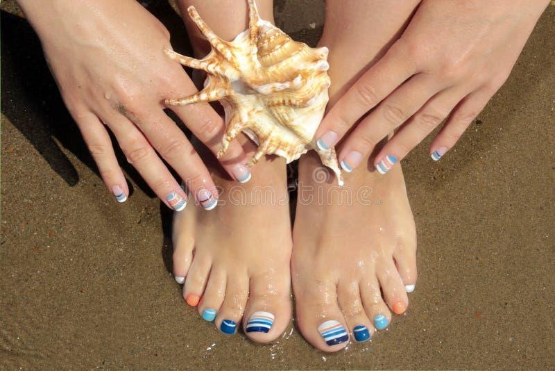 Θαλάσσια γαλλικά μανικιούρ και pedicure με τα μπλε και πορτοκαλιά λωρίδες στα κοντά καρφιά στην ακτή στοκ εικόνες