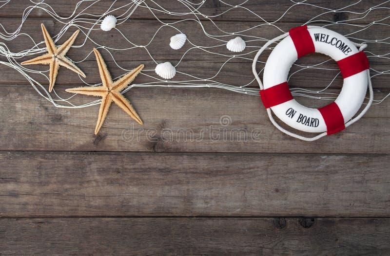 Θαλάσσια διακόσμηση με τα κοχύλια, αστερίας, πλέοντας σκάφος, δίχτυ του ψαρέματος στο μπλε ξύλο κλίσης στοκ φωτογραφίες