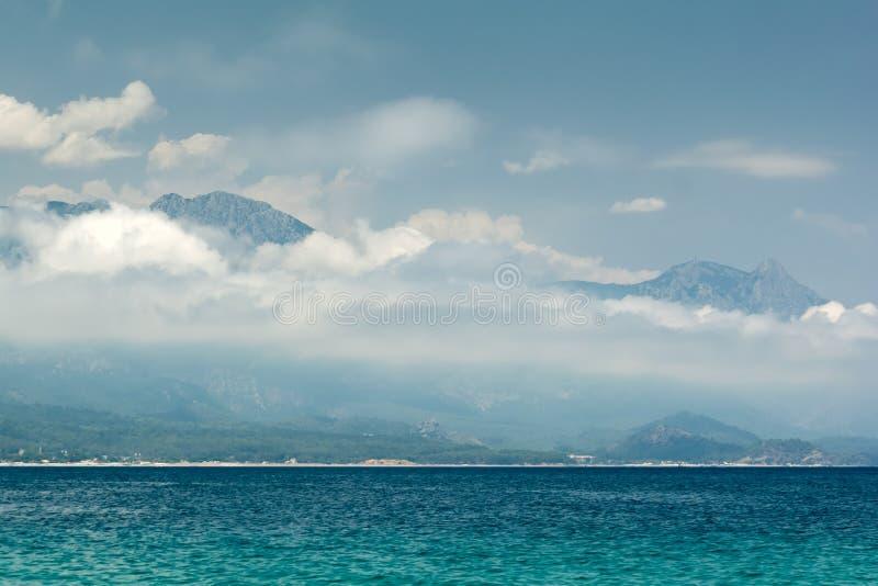 Θαλάσσια θέα στα όρη Ταύρου καλυμένη αριό χαηλά σύννεφα και τη Μεσόγειο αριό βάρκα Έννοια του ταξιδιού στοκ εικόνες