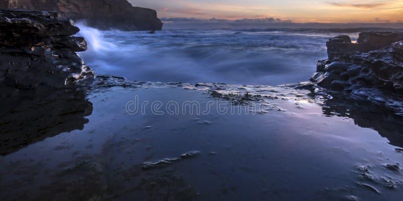 Θαλάσσιο νερό που συντρίβει στους βράχους στο Σαν Ντιέγκο στο ηλιοβασίλεμα στοκ εικόνες
