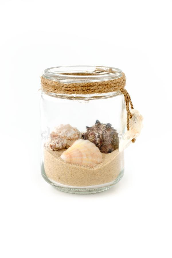 Θαλασσινά κοχύλια και άμμος σε ένα βάζο γυαλιού που απομονώνεται στο λευκό στοκ φωτογραφίες