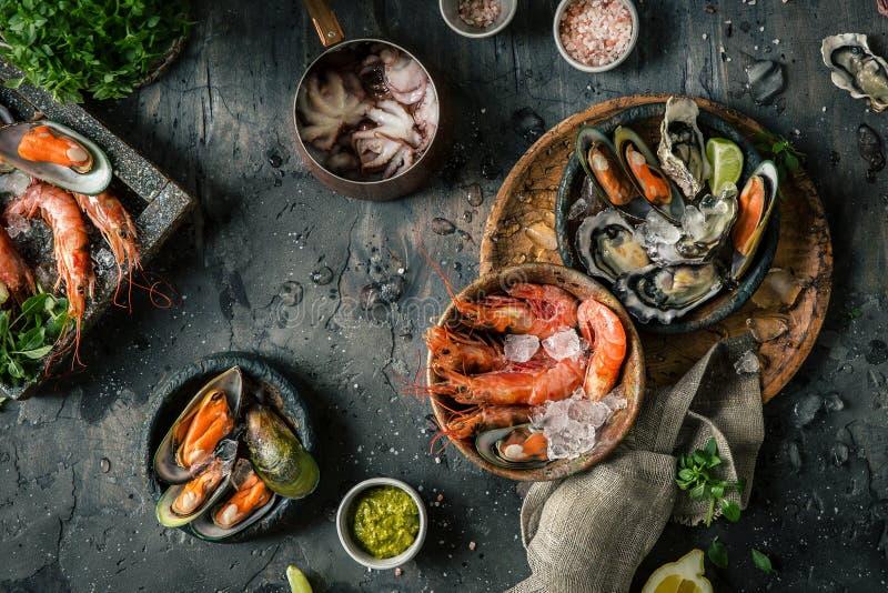Θαλασσινά Φρέσκες γαρίδες, στρείδια, μύδια, langoustines, χταπόδι στον πάγο με το λεμόνι στοκ εικόνες