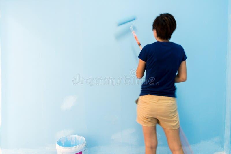 Θαμπάδα κινήσεων, πλάτη της γυναίκας που χρωματίζει τον μπλε τοίχο στο δωμάτιο στοκ φωτογραφίες