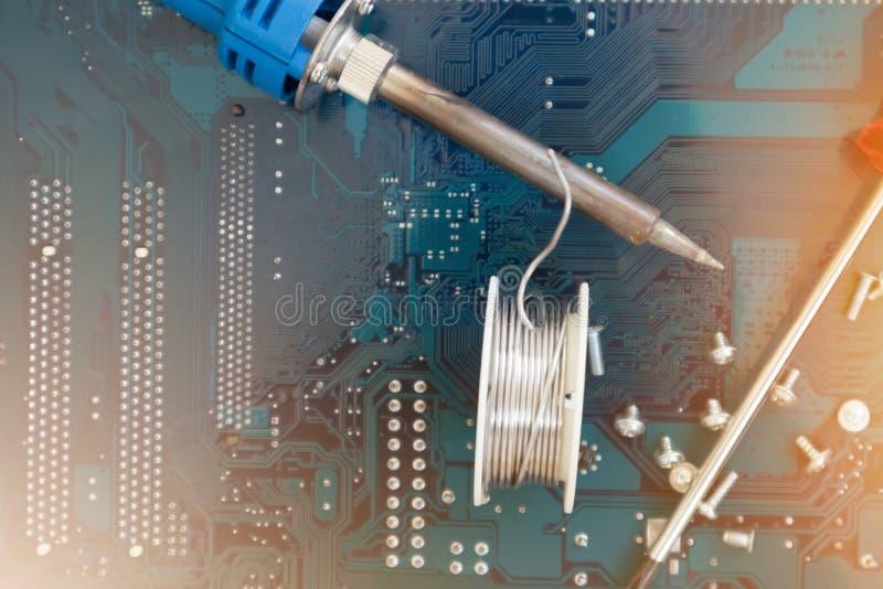 Θαμπά εργαλεία εικόνας για τεχνική επιδιόρθωση συγκόλληση σιδήρου και κατσαβιδιού στο ολοκληρωμένο κύκλωμα μητρικού πλακιδίου η στοκ εικόνες