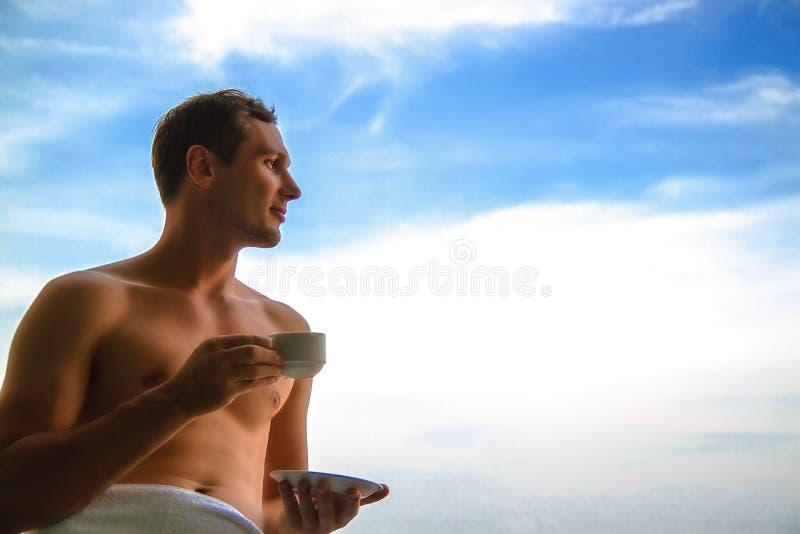 Θαυμάσια ημέρα Όμορφος εύθυμος τύπος που στέκεται στο μπαλκόνι κάτω από τον όμορφο ουρανό και που απολαμβάνει το ηλιόλουστο πρωί στοκ φωτογραφίες με δικαίωμα ελεύθερης χρήσης