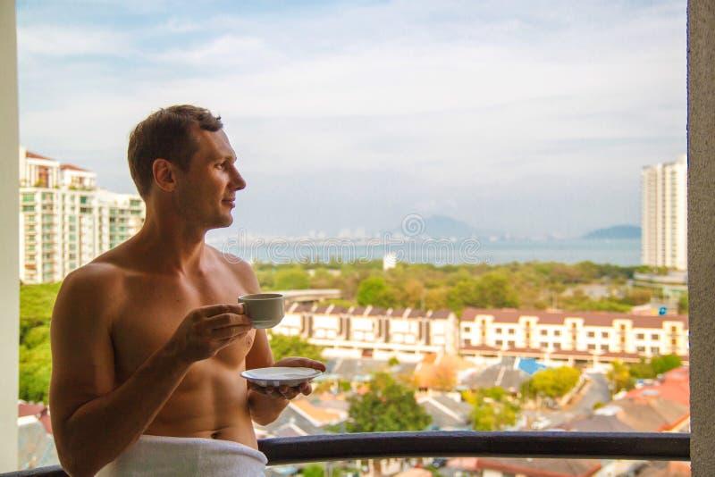 Θαυμάσια ημέρα Όμορφος εύθυμος τύπος που στέκεται στο μπαλκόνι κάτω από τον όμορφο ουρανό και που απολαμβάνει το ηλιόλουστο πρωί στοκ εικόνες