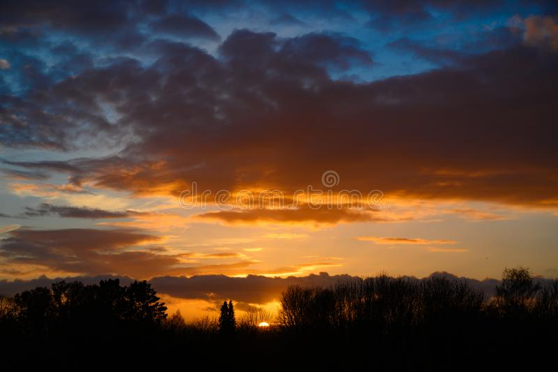 Θαυμάσιος ουρανός βραδιού με τα πορτοκαλιά σύννεφα στο ηλιοβασίλεμα πίσω από τα γυμνά δέντρα στοκ εικόνα με δικαίωμα ελεύθερης χρήσης
