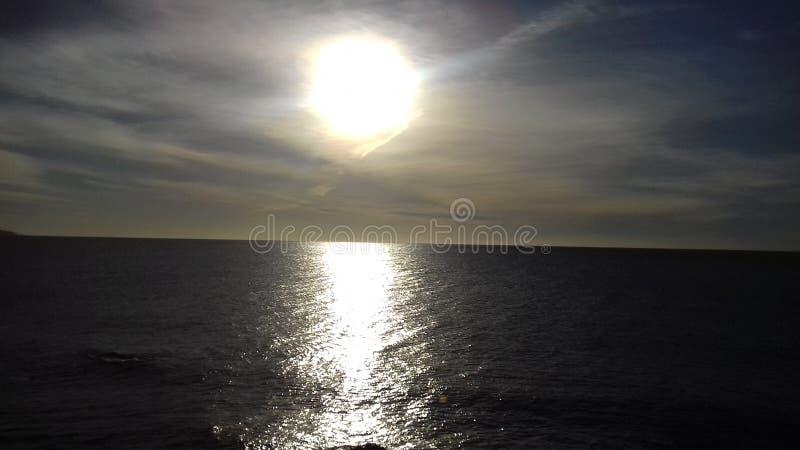 Θαυμάσιος τεράστιος ήλιος που λάμπει κάτω στην ήρεμη θάλασσα στοκ εικόνα