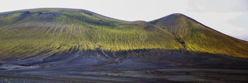 Θαυμάσιο ηφαιστειακό τοπίο στο δρόμο σε Landmannalaugar, Ισλανδία Μαύρη ηφαιστειακή τέφρα που καλύπτεται από τα πράσινα βρύα στοκ φωτογραφία