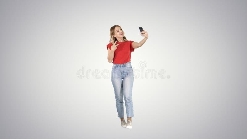Θαυμάσιο θηλυκό πρότυπο κλίσης που κάνει selfie περπατώντας στο υπόβαθρο κλίσης στοκ φωτογραφία με δικαίωμα ελεύθερης χρήσης