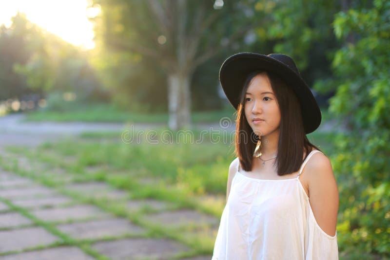 Θαυμάσιο θηλυκό καπέλων ασιατικό γέλιο συγκινήσεων ηλιοβασιλέματος εύθυμο στοκ φωτογραφίες