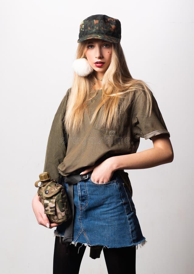 Θαυμάσιο λευκό κορίτσι στα στρατιωτικά ενδύματα που θέτουν με τη φιάλη Πορτρέτο στούντιο της όμορφης κυρίας στο κοίταγμα φουστών  στοκ φωτογραφία με δικαίωμα ελεύθερης χρήσης