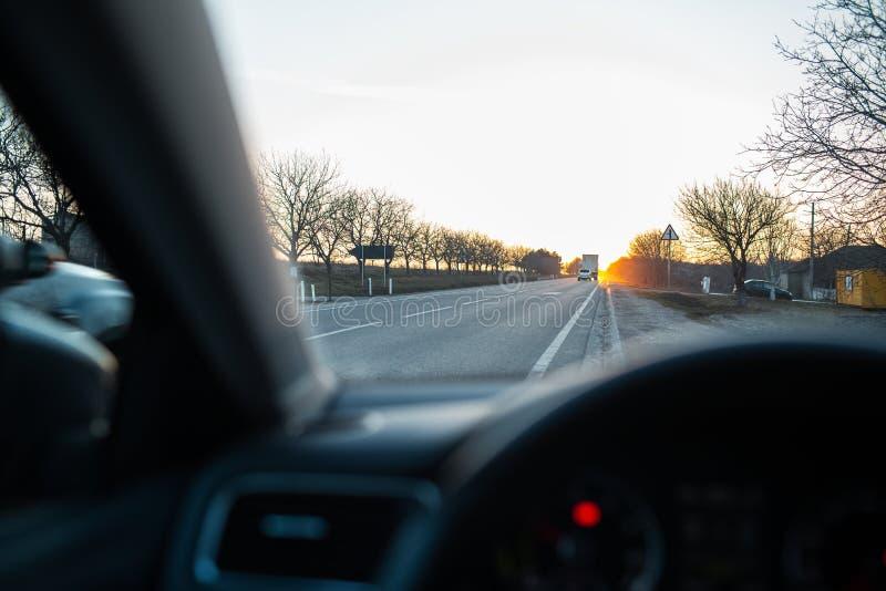 Θαυμασμός του ηλιοβασιλέματος μέσω του παραθύρου αυτοκινήτων στοκ φωτογραφίες