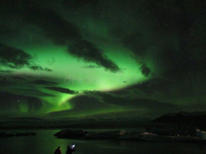 Θαυμασμός των τρομερών βόρειων φω'των που χορεύουν πέρα από τη λιμνοθάλασσα παγετώνων Jokulsarlon, Ισλανδία στοκ εικόνες