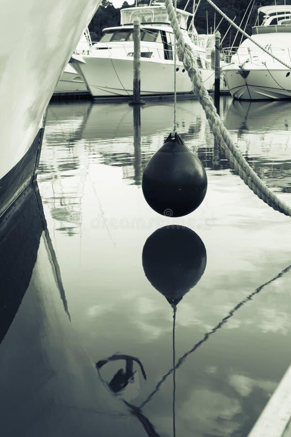 Θαλάσσιος σημαντήρας που κρεμά ανωτέρω - νερό μεταξύ των δεμένων βαρκών σε Tutukaka στοκ εικόνες με δικαίωμα ελεύθερης χρήσης