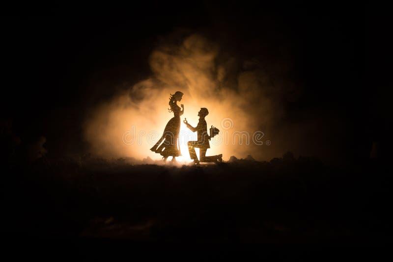 Θα με παντρεψετε; Σκιαγραφία του νεαρού άνδρα που μένει στο γόνατο και που κάνει την πρόταση για το καλό κορίτσι του στην παραλία στοκ φωτογραφία με δικαίωμα ελεύθερης χρήσης