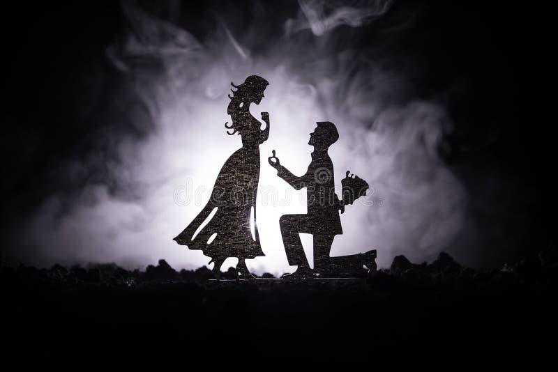 Θα με παντρεψετε; Σκιαγραφία του νεαρού άνδρα που μένει στο γόνατο και που κάνει την πρόταση για το καλό κορίτσι του στην παραλία στοκ φωτογραφίες