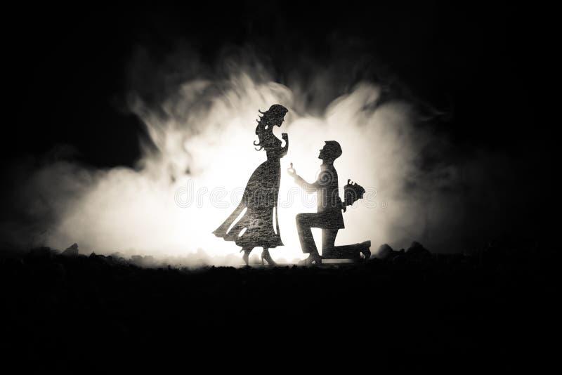 Θα με παντρεψετε; Σκιαγραφία του νεαρού άνδρα που μένει στο γόνατο και που κάνει την πρόταση για το καλό κορίτσι του στην παραλία στοκ εικόνες
