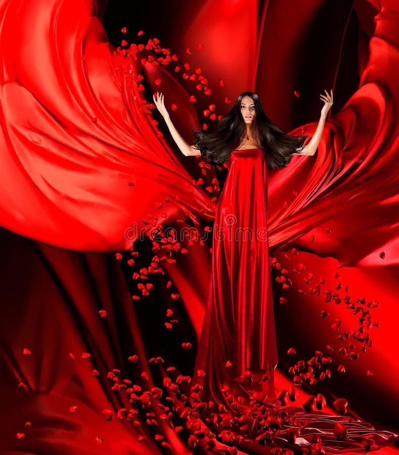 Θεά της αγάπης στο κόκκινο φόρεμα με τη θαυμάσιες τρίχα και τις καρδιές επάνω στοκ φωτογραφία