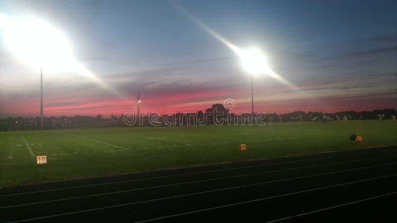Θεαματικό ηλιοβασίλεμα στο ποδοσφαιρικό παιχνίδι γυμνασίου στοκ εικόνες