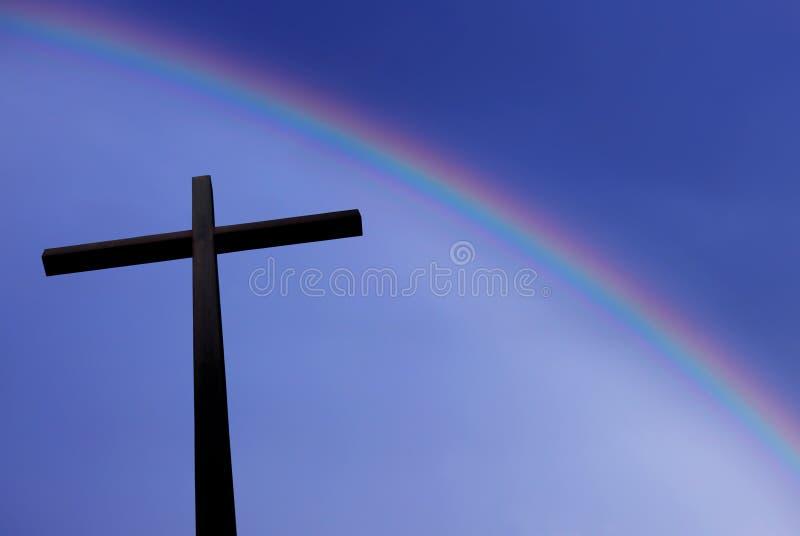 Θεαματικό ουράνιο τόξο επάνω από το χριστιανικό σταυρό στοκ εικόνα