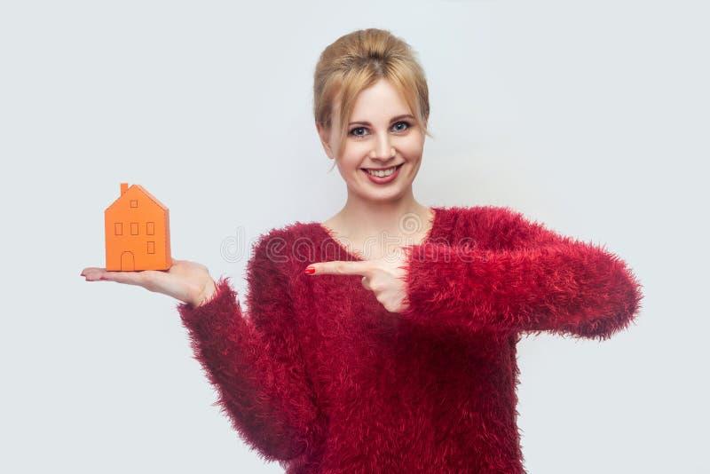 Θελήστε εσείς είναι κύριος του σπιτιού; Η ευτυχής νέα γυναίκα realtor στην κόκκινη μπλούζα που στέκεται, κρατώντας το κίτρινο μικ στοκ εικόνα