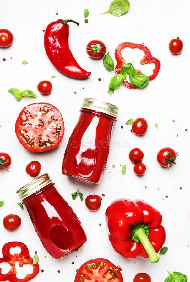 Θελήστε κάποιο χυμό; Εξαιρετικά φωτεινός, κόκκινος, φρέσκος χυμός θερινών πικάντικος ντοματών με το πιπέρι, άλας και καρυκεύματα, στοκ εικόνες