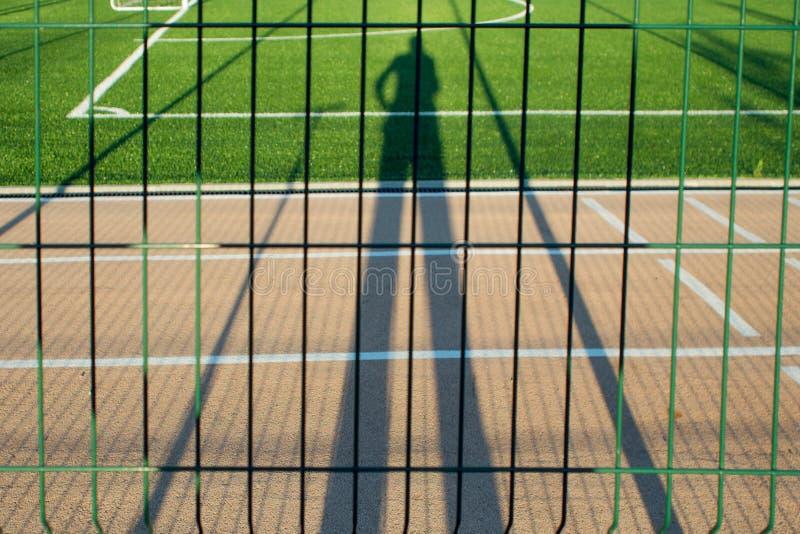 Θελήστε να παίξετε τον αθλητισμό, πρόσωπο που προσέχει την παιδική χαρά μέσω του φράκτη, σκιά στοκ εικόνες