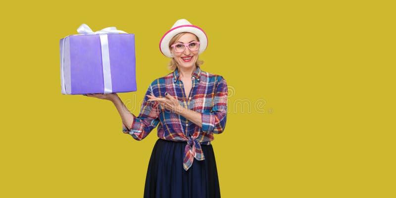 Θελήστε το παρόν; Ευτυχές όμορφο σύγχρονο grandma στο άσπρο καπέλο και στην ελεγμένη στάση πουκάμισων, που κρατά το μεγάλο κιβώτι στοκ φωτογραφίες